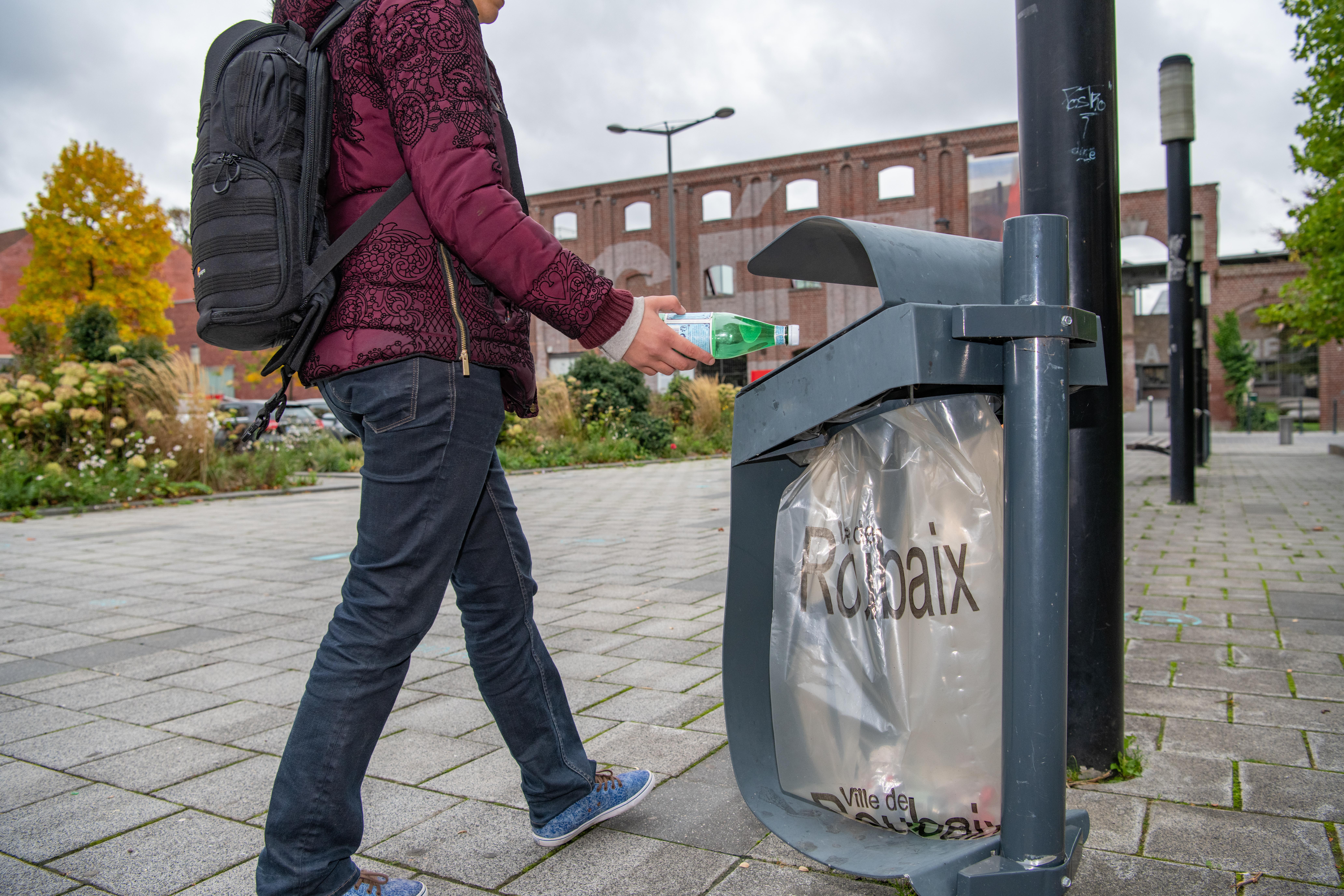 citoyen jetant une bouteille dans une poubelle publique